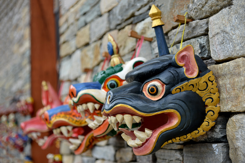 Beautiful hand crafted painted wood-masks made by an artist sitting outside the National Library and Archives and Foreign Language Library Block of Bhutan at Thimphu, Bhutan.
