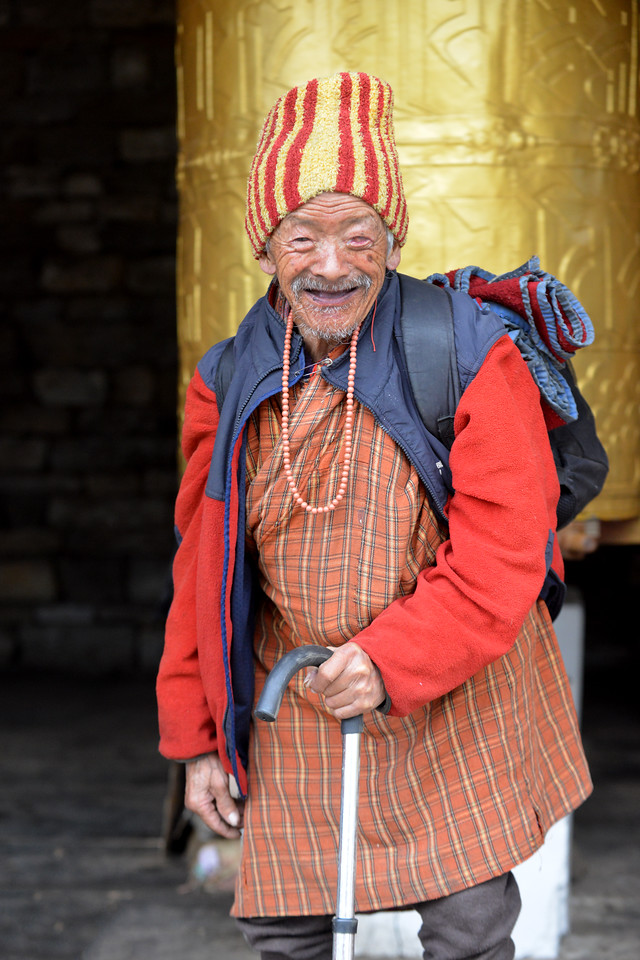Old man who is a regularaat the Memorial Chorten, Chhoten Lam, Thimphu, Bhutan offering prayers at the buddhist prayer wheels.