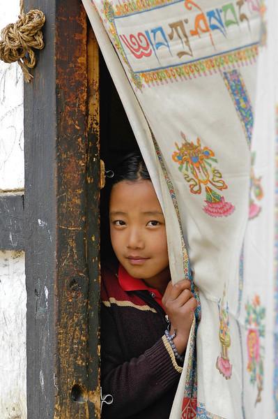 Young girl peeping from her home in Thimpu, Bhutan.