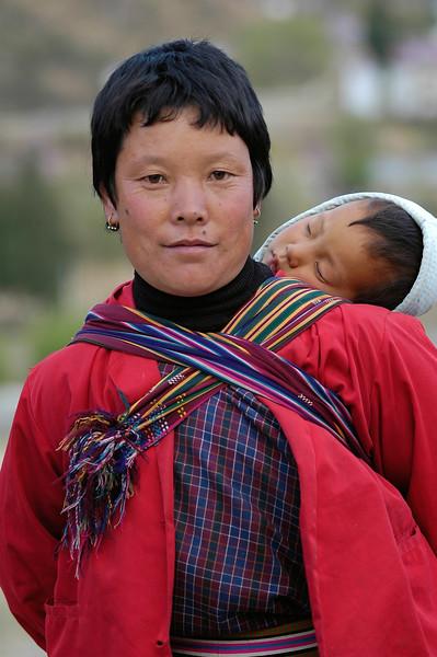 Mother carrying her sleeping child in Bhutan.