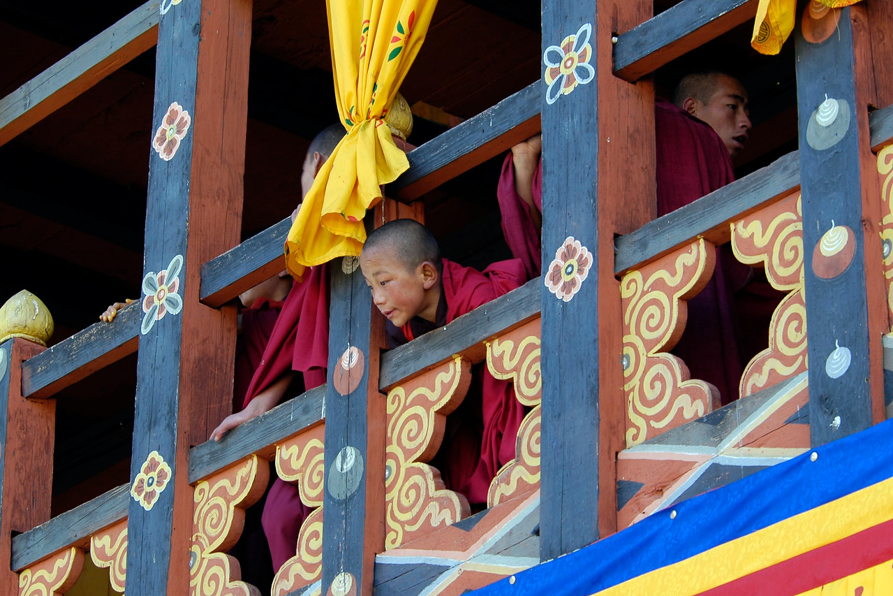 Curious young monks peepking from the windows at the Paro Tsechu Festival of Dance held in Paro, Bhutan. This is the biggest and most spectacular Buddhist festival celebration.
