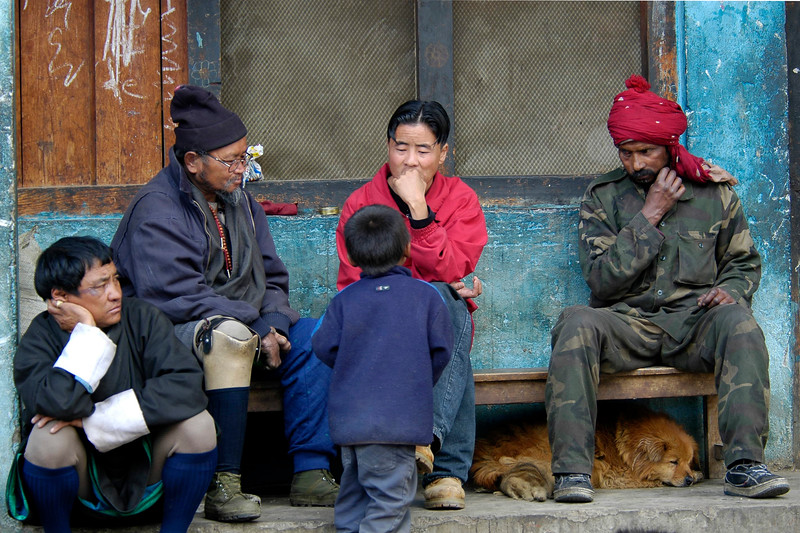 Elders listen to a child with a dog lazing below the bench. Thimphu, the capital of Bhutan.