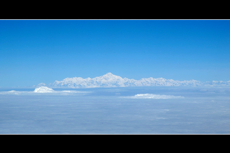 View from the Druk Air flight between Kolkata and Paro, Bhutan. The Himalayan range is clearly visible and makes a lovely sight. Clear blue sky with mountain peaks rising above the clouds.