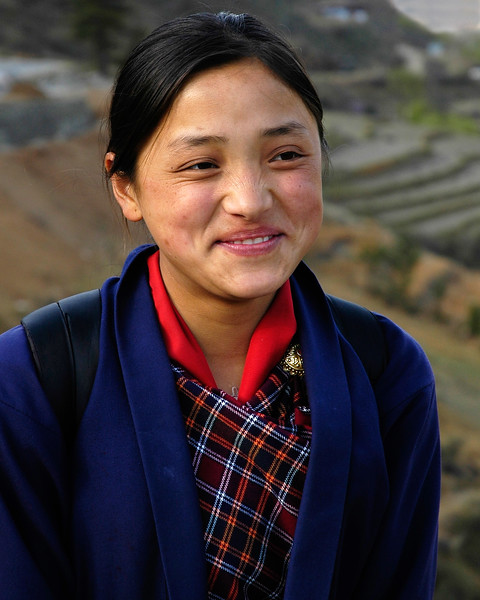 Bhutanese School Girl [Bhutan]. This girl dressed in her school dress was returning to her home. In the backdrop are the Govt. buildings of Bhutan in Thimpu.