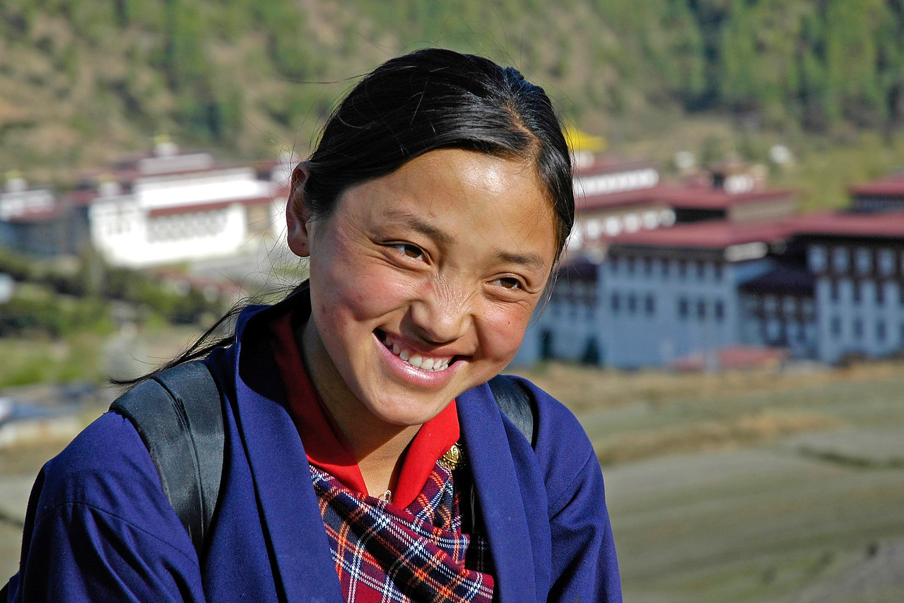 Bhutanese School Girl [Bhutan]<br /> This girl dressed in her school dress was returning to her home.<br /> In the backdrop are the Govt. buildings of Bhutan in Thimpu.
