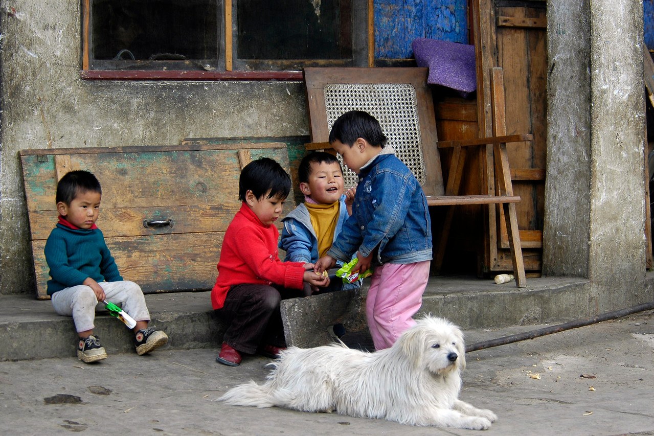 Kids playing in the streets of Thimphu, the capital of Bhutan while a dog watches on.