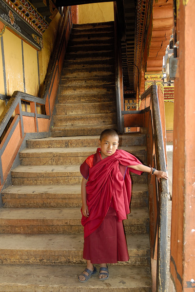 Young monk in Paro, Bhutan walking down the steps of the monastry.