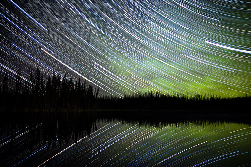 Star trails, aurora borealis and silhouetted trees, Blue Lakes, Northern British Columbia, Canada.