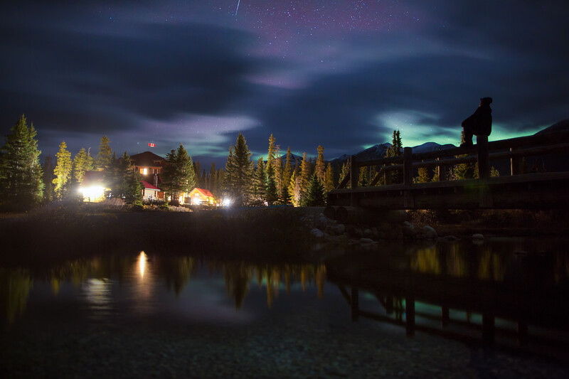 Person overlooking lodge under night sky