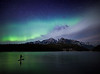 Stand up paddle boarder at Two Jack Lake under Aurora