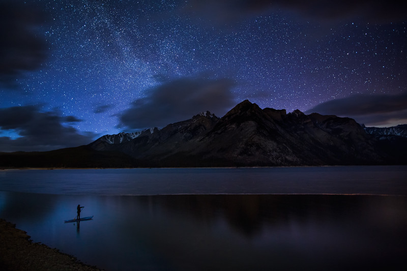 SUP Lake Minnewanka under night sky