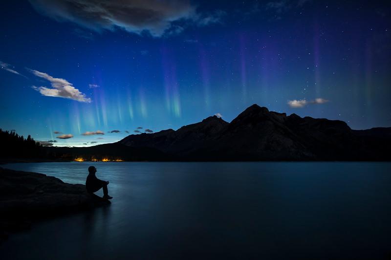 Man watching Aurora Borealis, Lake MInnewanka