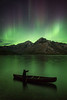 Canoe at Lake Minnewanka under Aurora Borealis