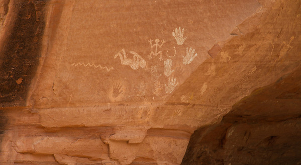 Petroglyphs (design scratched into the rock surface -- like the snake and handprints on top) and pictographs (designs made by spraying paint over hand -- like dark handprints on lower portion of the wall).