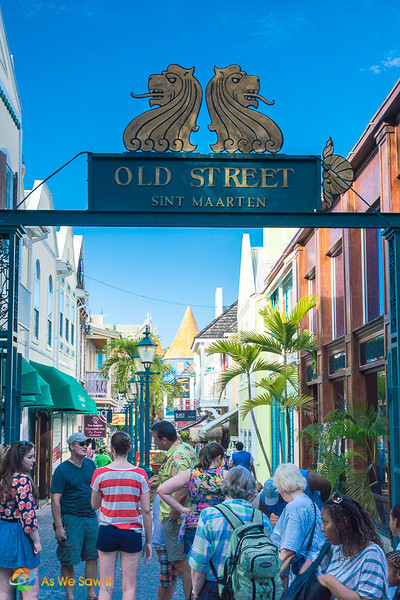Tourists on a pedestrian side street in Philipsburg. Sign overhead says Old Street Sint Maarten.