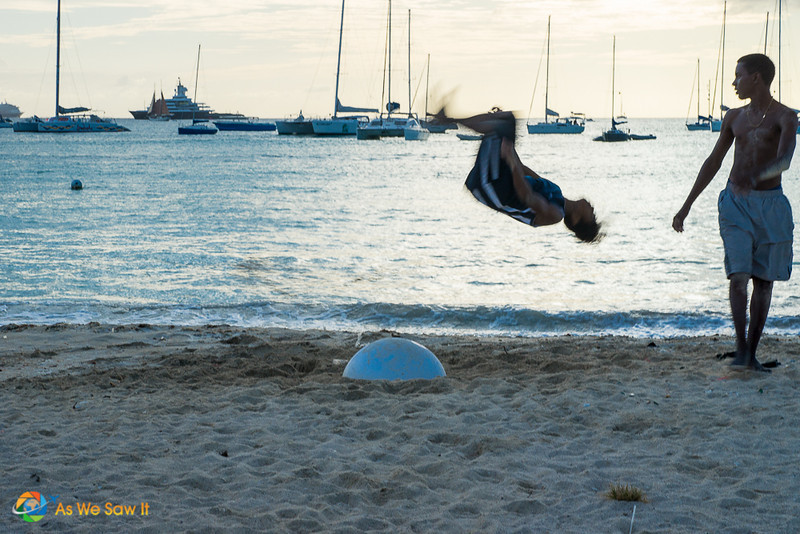 Teen in the midst of a flip. Sailboats in the background.