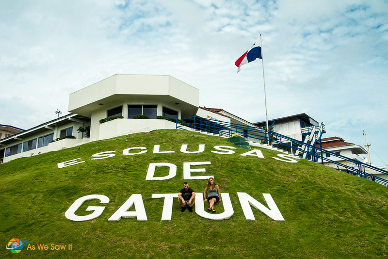 2 people pose at Gatun locks sign on the Caribbean side of the Panama Canal. A favorite day trip from Panama City.