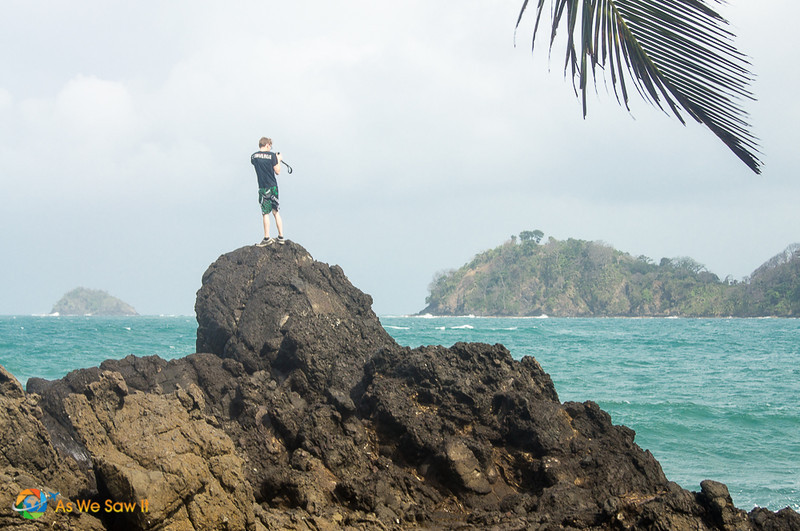 Isla Grande is one of the best day trips from Panama City. Here, our son stands on a rock in the foreground, ready to photograph the turquoise Caribbean water and hill outcrop in the distance.