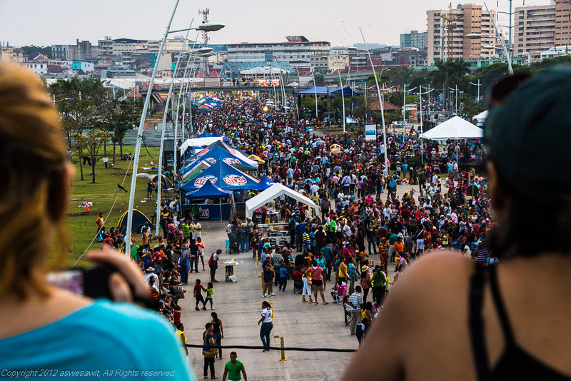 Two people in foreground watch Panama Carnival crowds