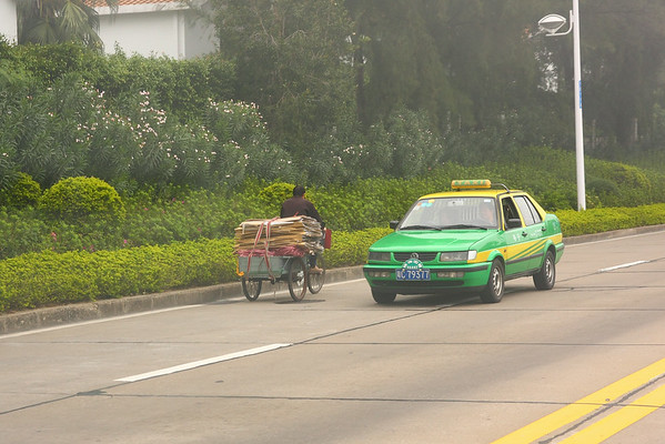A loaded  tricycle sharing the road, in this case, going against traffic. Also, all taxis in Zhuhai were VW Jettas.