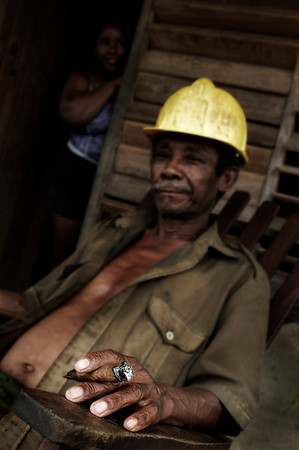 Worker relaxing with a cigar outside his home. Wife in the background, Vinales,   Cuba , 2006