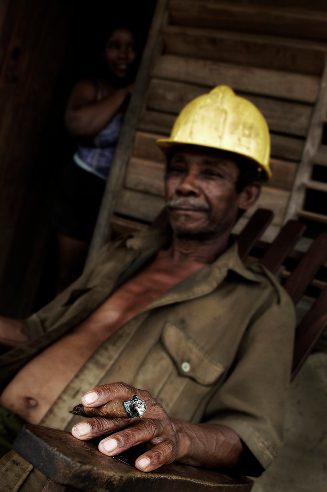 Worker relaxing with a cigar outside his home. Wife in the background, Vinales, <br /> <br /> Cuba , 2006