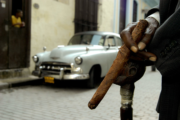 Cuban cigars and 50's American cars are emblematic sights in Havana.  Cuba, 2006.
