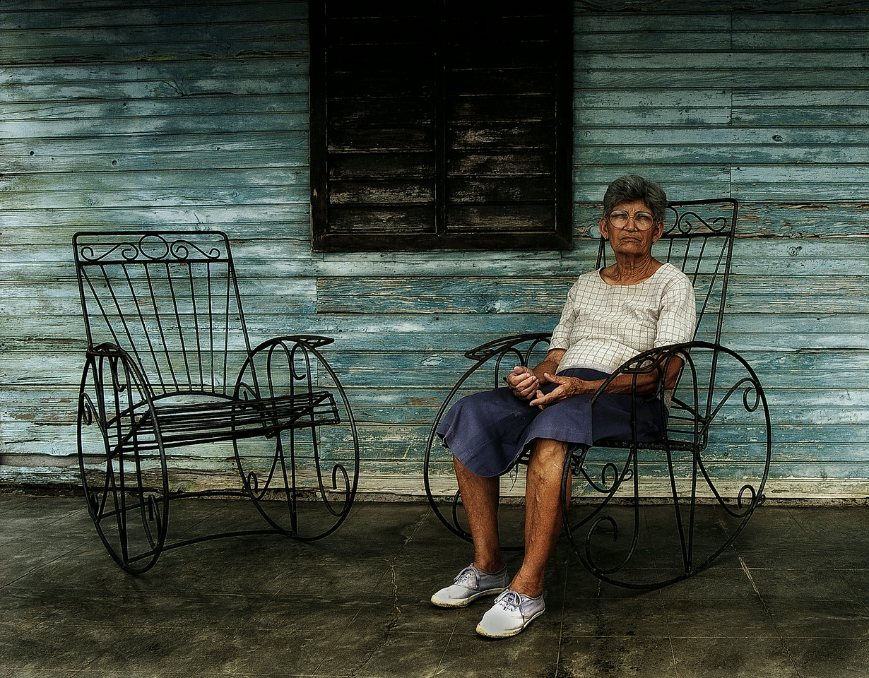 Sitting in the shade on the front porch seems to be the local pastime in Cuba. And what could be better than rocking the evenings away on a finely crafted rocking chair? Every house has at least two of these cast iron giants on their porch. <br /> <br /> Country house, Central Cuba, 2006