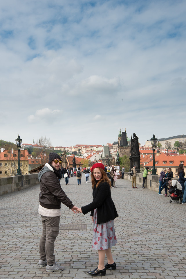 Many couples cross Vltava river on Charles Bridge, Prague (Praha), Czech Republic taking pictures, making wishes and enjoying the view.
