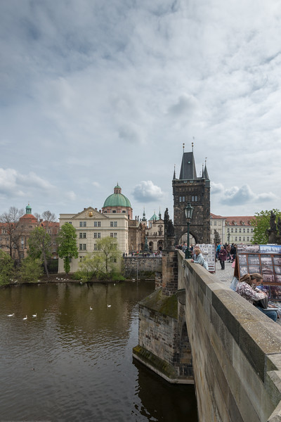 Tower and Saint Francis of Assisi Church seen from Charles Bridge, Prague, Czech Republic.<br /> <br /> The Charles Bridge (Czech: Karlův most) is a famous historic bridge that crosses the Vltava river. Its construction started in 1357 under the auspices of King Charles IV, and finished in the beginning of the 15th century. The avenue of 30 mostly baroque statues and statuaries situated on the balustrade forms a unique connection of artistic styles with the underlying gothic bridge. They depict various saints and patron saints venerated at that time.