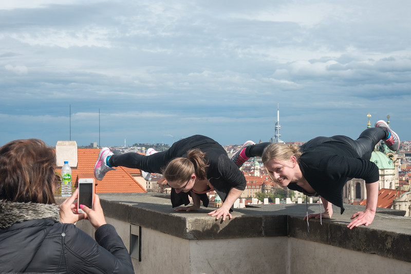 Girls doing crazy stunts on the viewing area wall of Prague Castle which has a steep drop at the back. Prague, Czech Republic.