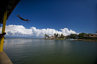 Boy diving off roof into the river in Dangriga Town.