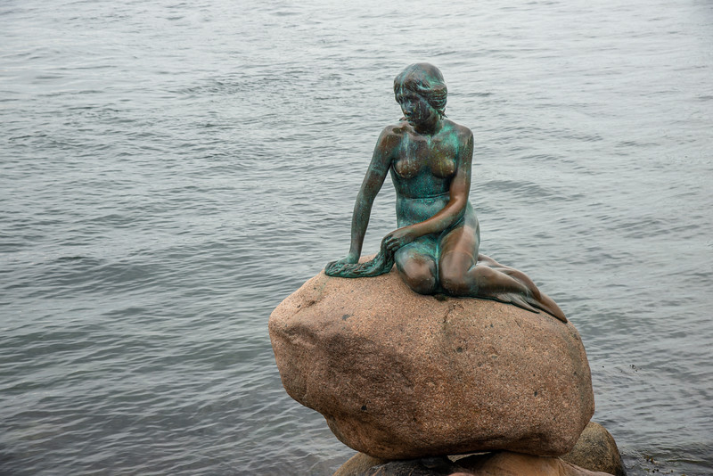Sad looking mermaid sitting on a rock. The Little Mermaid, Den Lille Havfrue, Langelinie, København, Copenhagen, Denmark. Iconic bronze mermaid sculpture, by Edvard Eriksen, of a character from H.C. Andersen's fairytale.