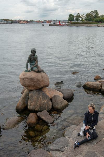 Tourists that flock to the mermaid statue try and emulate her pose. The Little Mermaid, Den Lille Havfrue, Langelinie, København, Copenhagen, Denmark. Iconic bronze mermaid sculpture, by Edvard Eriksen, of a character from H.C. Andersen's fairytale.