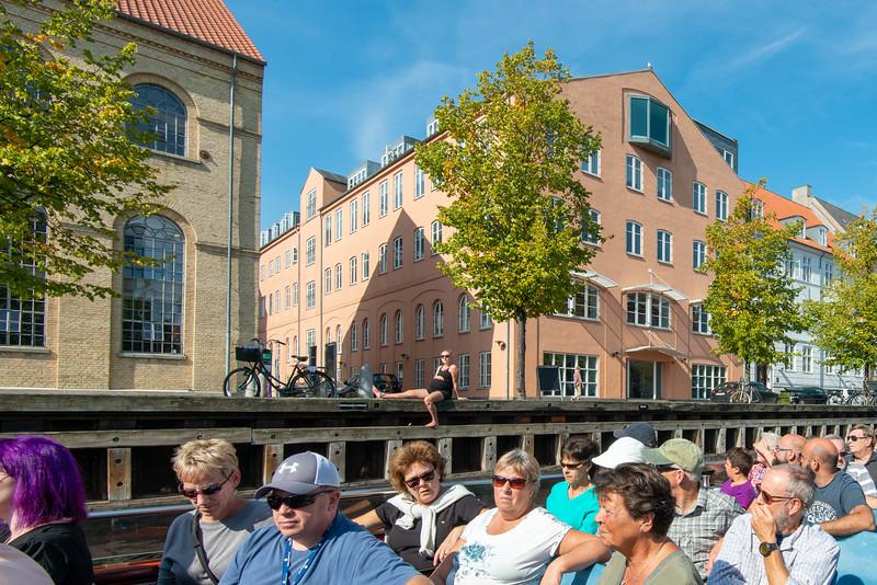 Pregnant lady sunbathing along the canal. Copenhagen Canal Tour. Copenhagen, København, Denmark.