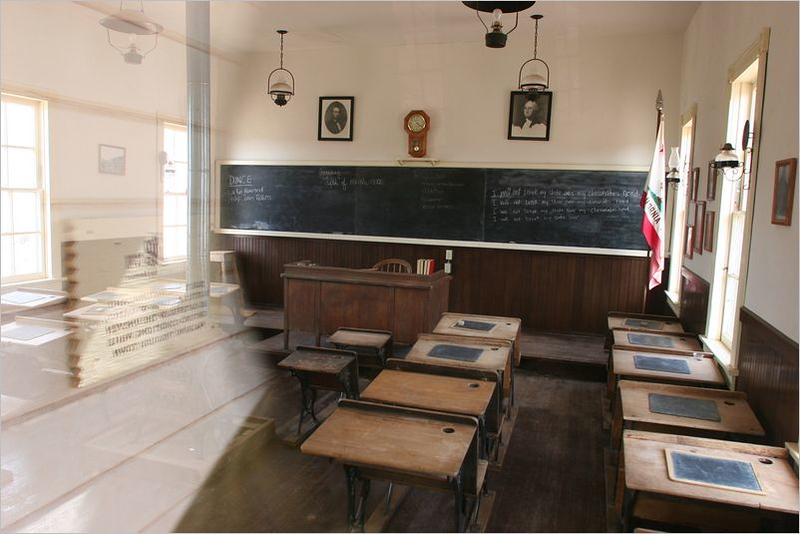 "Inside the school house<br /> The chalkboard reads, ""I will not break my slate over my classmates head."""