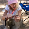 Megan practises her whittling skills with her safety knife.  Note the Mini Mag light too.  This is one prepared little girl!