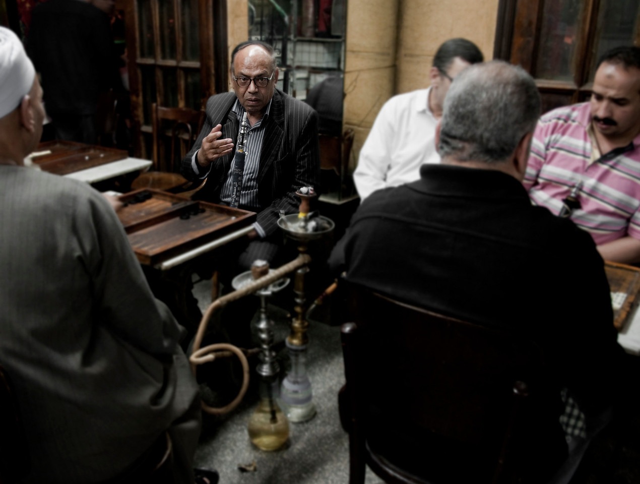 Cairenes playing Backgammon and smoking shisha in one of the many Ahwas or cafes found around Cairo. <br /> <br /> Egypt, 2010.