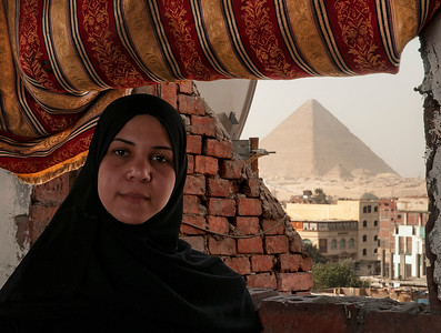 A local woman from one of the neighborhoods around the Pyramids inside her home. The view of the Pyramids from her window.  Cairo, Egypt, 2010