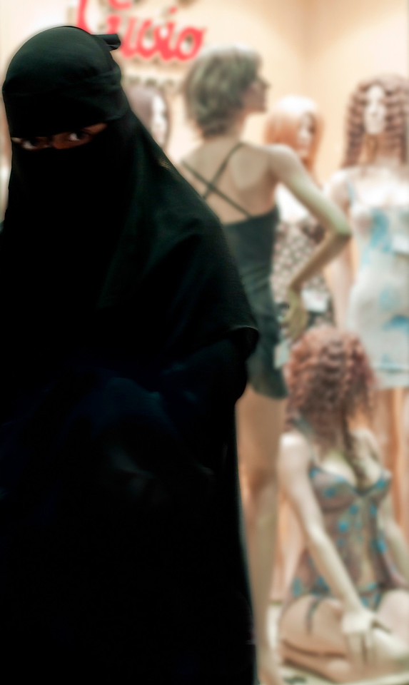 Woman coming out from a lingerie shop in central Cairo. <br /> <br /> Egypt, 2010.
