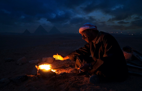 A local desert guide warming his hands on a campfire with the pyramids of Giza in the background.  Cairo, Egypt, 2010