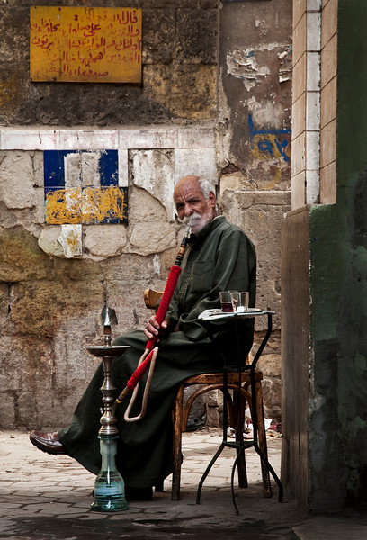 Man smoking shisha outside an ahwa in the  Darb-al-Ahmar residential district. <br /> <br /> Cairo, Egypt, 2010.