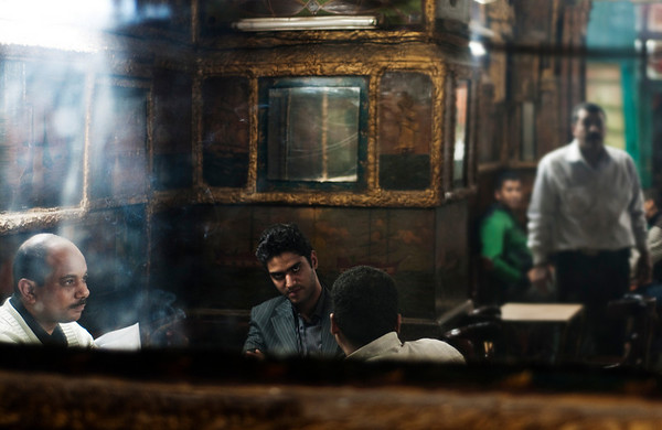 Smoke from shisha or water pipes, sawdust on the floor, misty mirrors and intriguing gazes are all part of the Ahwas or cafe culture in Cairo. This is where the local men gather for a game of back gammon, domino's or just to discuss the local politics.   Cairo, Egypt, 2010.