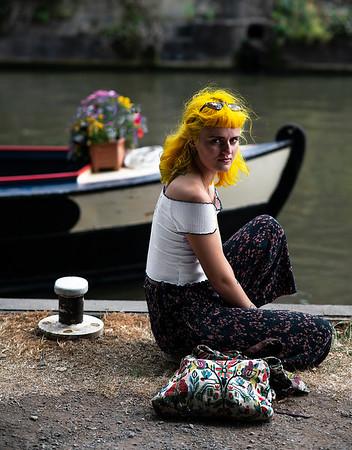 A young woman relaxes by the canals in the city of Bath.  Bath, somerset, England, 2018.