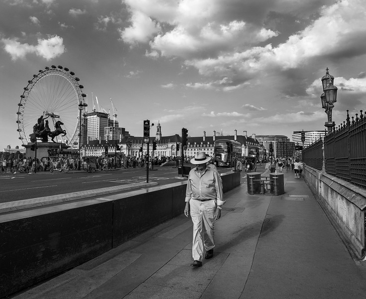 Man walking over a bridge in the city of London.  London, England, 2018
