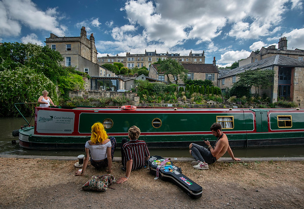 Youngsters chilling by a canal watching the boats go by.  Bath, Somerset, England, 2018.