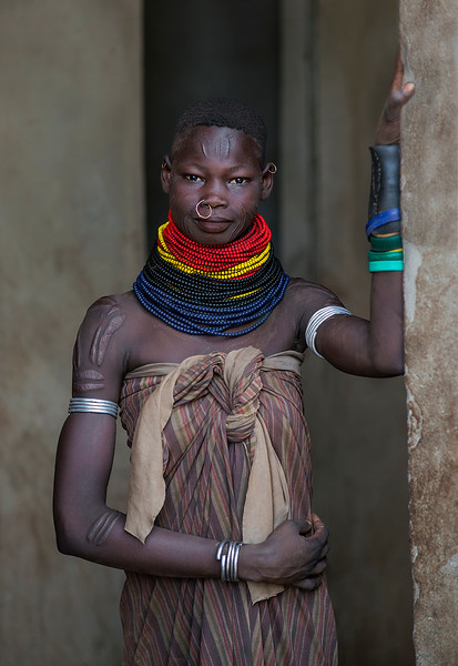 Heavy necklaces and long skirts from goat skins, which are richly decorated, are characteristic for the Nyangatom women. Necklaces were traditionally made from dry seeds, but these days they have been largely replaced with colourful glass beads coming from Kenya. The women also decorate themselves with ornamental scarification on their faces, chests, and bellies. <br /> <br /> Omo valley, Ethiopia, 2017.