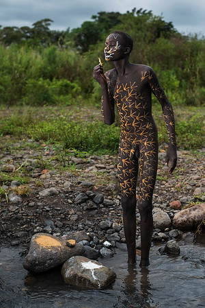 A young Suri man painting his body in the traditional way down by the river.  Southern Ethiopia 2017.