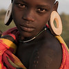 A young Murci girl wearing the traditional earnings made of clay.<br /> <br /> Omo Valley, Ethiopia, 2017.