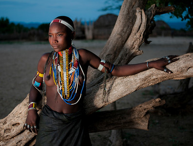 This is Guri, a young woman from the Arbore tribe. Arbore, unmarried women shave there head as a sign of there virginity, once married they are allowed to grow there hair. As part of the marriage preparations Arbore women need to be Circumcised. Whilst their mothers hold them down they have there Clitoris removed with a sharp knife. They then need to spend a couple of months indoors before resuming there marriage life.  Omo Valley, Southern Ethiopia, 2013.